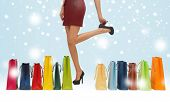 shopping, sale, gifts, christmas, x-mas concept - woman's long legs with shopping bags and shoes