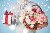 valentine's day, christmas, x-mas, winter, happiness concept - man holding basket full of flowers and gift box.