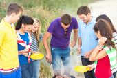 summer, holidays, vacation, happy people concept - group of friends having picnic and making barbecu
