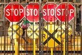 stock photo of railroad-sign  - Stop railroad crossing signs behind bars at a amusement park - JPG
