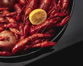 stock photo of crawfish  - red boiled crawfish on a plate with lemon - JPG