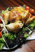 Platter Of Delicious Roast Chicken Turkey With Salad Greens And Red Tomatoes On The Vine For A Succu