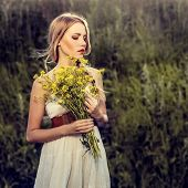 image of slender  - portrait of a beautiful girl with flowers in the forest