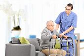 Male nurse helping an elderly gentleman to stand up in a nursing home