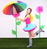 Beautiful young woman in petty skirt with umbrella on decorative background