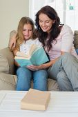 Girl and mother reading novel together on sofa at home