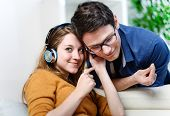 Attractive Young Couple Listening Music Together In Their Living Room At Home