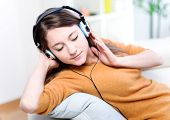 Beautiful Relaxed Young Woman Listening Of The Music By Being Lengthened On Its Sofa