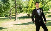 Full length portrait of handsome bridegroom standing in garden