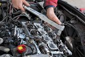 stock photo of overhauling  - Mechanic fixing cylinder head with two camshaft of car engine with socket wrench - JPG