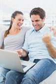 Excited couple sitting on the couch using laptop together at home in the living room