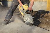 stock photo of sawing  - Asphalt or concrete cutting with saw blade at construction site - JPG