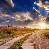 Road Of Concrete Slabs Uphill To The Sunset Sky