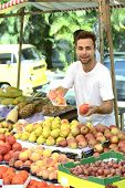 Greengrocer owner of a small business at at an open street market, selling organic fruits and vegeta
