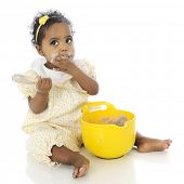 An adorable baby girl looking up as if innocent, while putting her hand over her mouth covered in pudding she's taking from the mixing bowl before her.  On a white background.