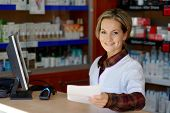 young smiling female pharmacist holding prescription
