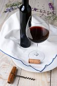 High angle wine and flower still life. Glass of red wine and bottle on a towel and wood rustic table. Vertical format.