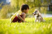 Young Asian boy playing with puppy on grass