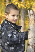 Smiling Boy In Autumn Forest.