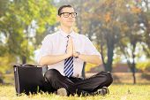 image of stressless  - Businessperson with eyeglasses doing yoga exercise seated on a green grass in a park - JPG