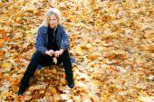 junge pronounced Frau sitzt auf Herbst Blätter