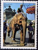 LAOS - CIRCA 1994: A stamp printed in Laos shows a man with a crown on an elephant circa 1994