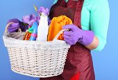 stock photo of spring-cleaning  - Housewife holding basket with cleaning equipment on color background - JPG