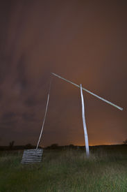 picture of shadoof  - Shadoof with moon at night illuminated with spotlight  - JPG