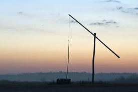 stock photo of shadoof  - Shadoof with orange and blue sky at sunrise - JPG