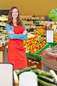 Smiling elderly saleswoman standing in a supermarket with her arms crossed