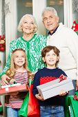 Happy children with grandma and grandpa at christmas holding gifts