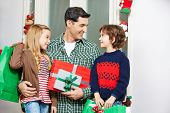 Happy father looking at two children with gifts at christmas