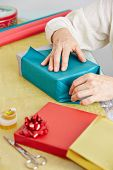 Old hands of senior woman wrapping a gift for christmas