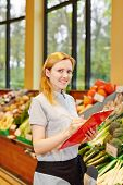 Smiling young woman as salesperson with clipboard in supermarkt