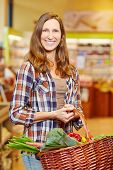 Smiling elderly woman carrying basket full of fresh vegetables in a supermarket