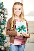 Smiling happy girl holding a present at christmas eve