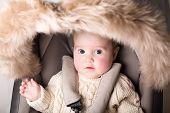 Sweet Baby With Big Beautiful Eyes Sitting In A Luxury Fur Stroller