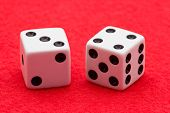 picture of crap  - Horizontal Photo of Two white dice with black dots displaying craps seven on two sides on red felt background - JPG