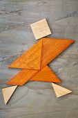 abstract of a dancing, running or walking figure built from seven tangram wooden pieces, a tradition
