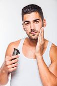 image of electric trimmer  - young handsome man in white shirt trimming his beard with a trimmer - JPG