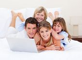 Smiling Family Looking At A Laptop Lying Down On Bed