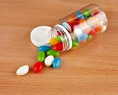 Colored Pills pouring out of the plastic bottle on surface wooden table