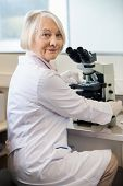 Portrait of confident senior female scientist using microscope in lab