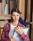 Portrait of confident female supervisor holding clipboard in workshop