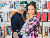 Portrait of confident female customer with hands folded standing against worker in hardware store