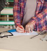 Midsection of worker drawing blueprint at table in workshop