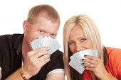 Man And Woman Smile Behind Playing Cards