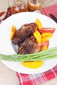 meat food : rare medium roast beef fillet with mango tomatoes and asparagus , served on white dish o