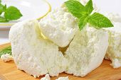 detail of fresh cheese slices on wooden cutting board