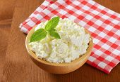 bowl of fresh cottage cheese on wooden table